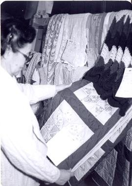 Woman looking at quilt, West Coast Mennonite Relief Sale