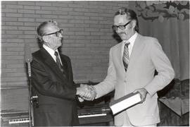 J. B. Toews presents a copy of P. M. Friesen's Mennonite Brotherhood in Russia to Abe Friese...