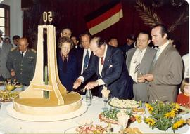 Paraguayan president Alfredo Stroessner cuts cake at celebration of Ferrnheim Colony's fifti...