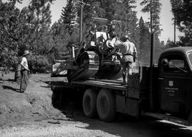 Unloading a bulldozer from truck at Civilian Public Service Camp #31