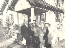 A.E., Philip, and Zola Janzen in front of their home