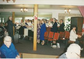 H.P. Neufeld conducting at Tabor home