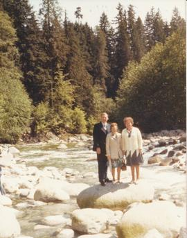 Three adults standing on rocks