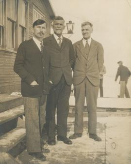 Three men in front of home