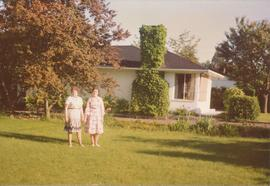 Two women on a lawn beside a home