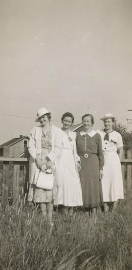 Four women standing in front of a fence