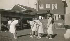 Four girls playing lawn croquet