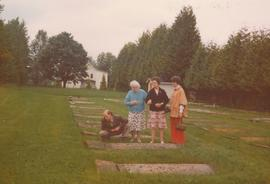 4 people examing gravestones