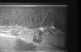 Unidentified man crossing river in pulley car (356.20)