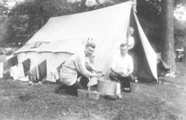 Three persons with a tent