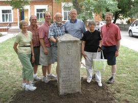 Descendants of Jacob D. Reimer posing with the relocated Reimer tombstone at the Molochansk Menno...