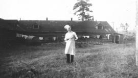 Cook standing in front of log building